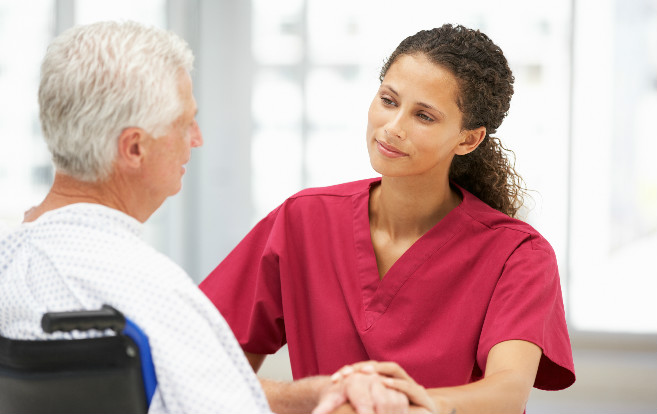 Ethnic_nurse_listening_senior_patient_in_wheelchair
