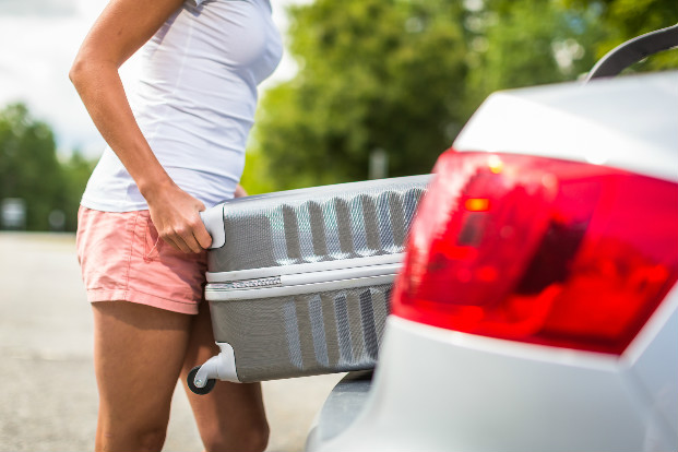 Woman_putting_suitcase_in_car