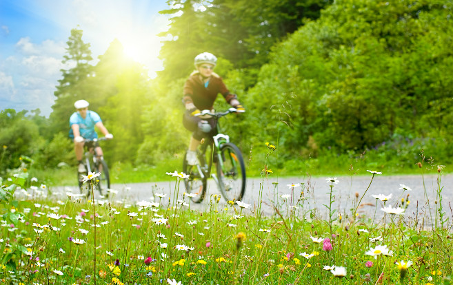 two_people_on_bikes_spring_exercise_couple_flowers